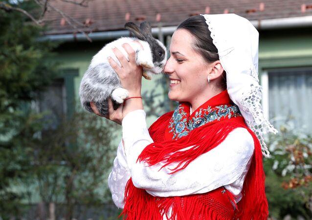 Kobieta w stroju ludowym z królikiem podczas uroczystości wielkanocnych na Węgrzech