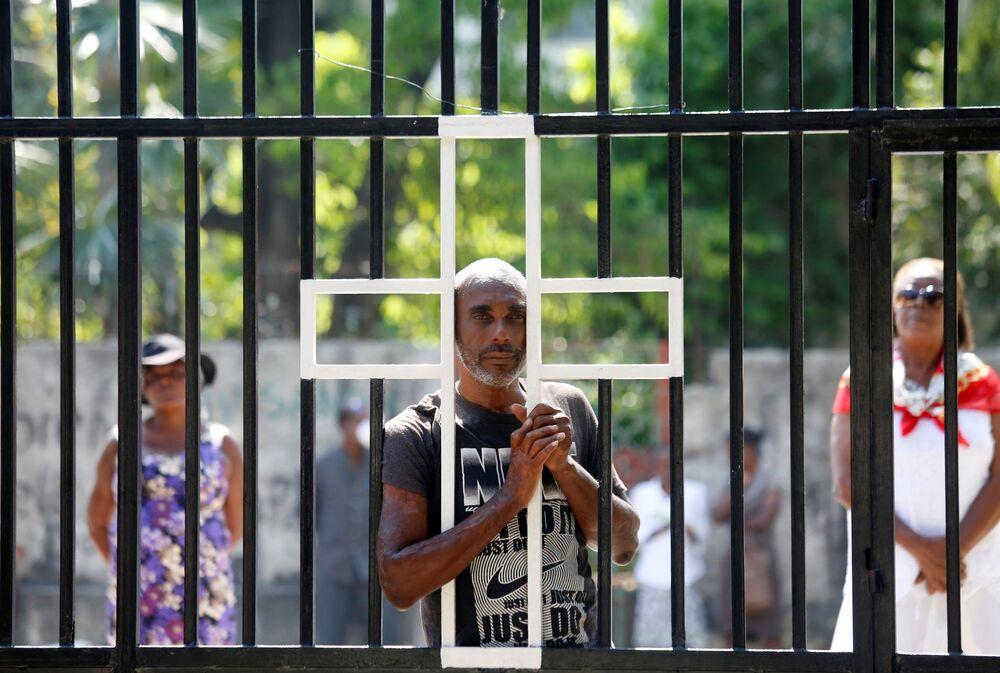 Ludzie przy zamkniętej bramie kościoła podczas świąt wielkanocych na Haiti