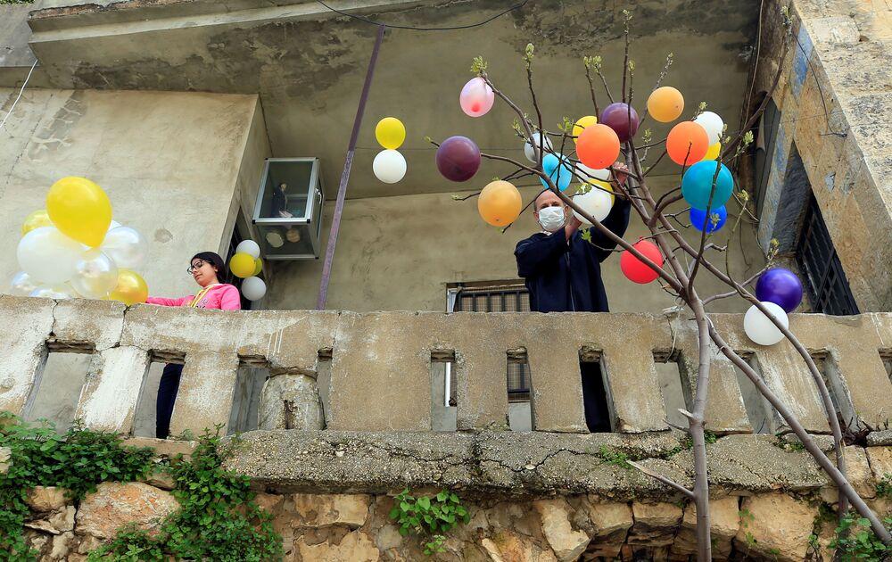 Mężczyzna ozdabia drzewo balonami podczas Wielkanocy w Libanie