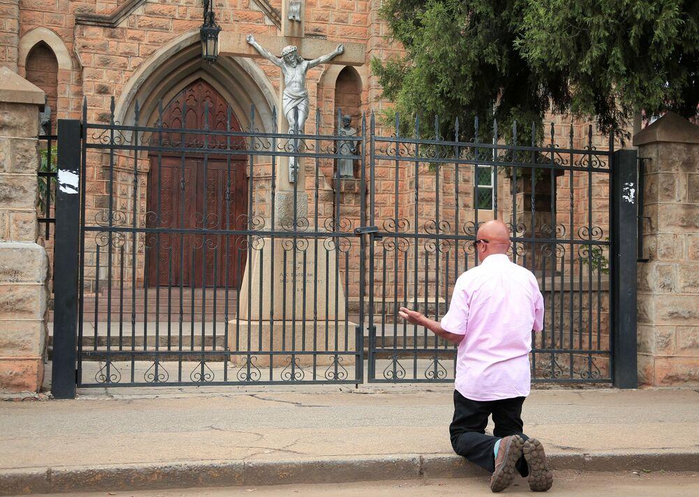 Mężczyzna modli się przed zamkniętym kościołem w Zimbabwe