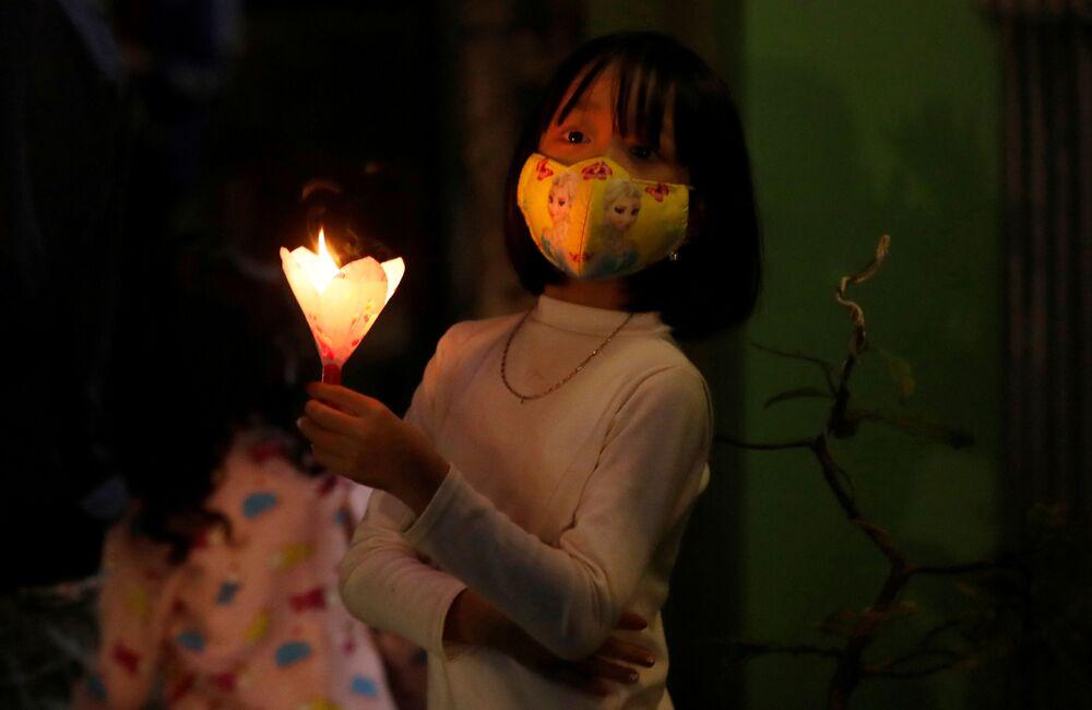 Dziewczynka w masce ochronnej podczas świąt wielkanocnych w Wietnamie