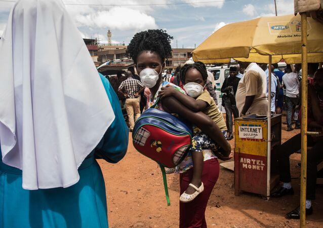 Matka z dzieckiem w maskach w Ugandzie