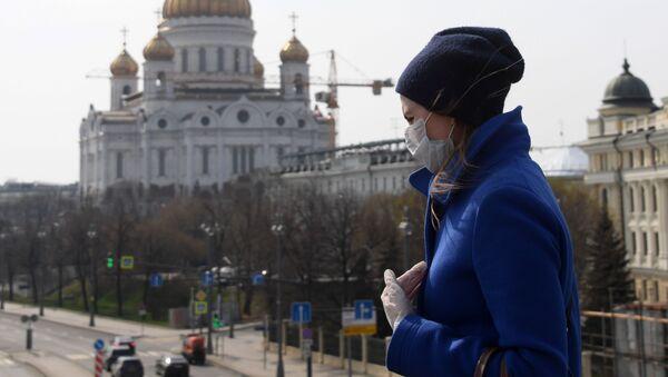 Kobieta w maseczce i rękawiczkach jednorazowych na tle Cerkwi Chrystusa Zbawiciela w Moskwie - Sputnik Polska