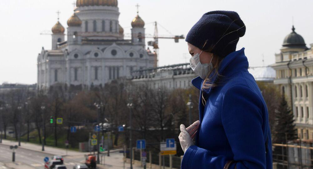 Kobieta w maseczce i rękawiczkach jednorazowych na tle Cerkwi Chrystusa Zbawiciela w Moskwie