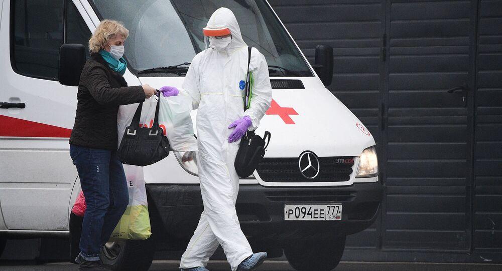 Lekarz pogotowia w kombinezonie ochronnym pomaga pacjentce przenieść rzeczy do centrum kwarantanny w Kommunarce