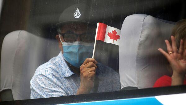 Mężczyzna w masce z flagą Kanady - Sputnik Polska