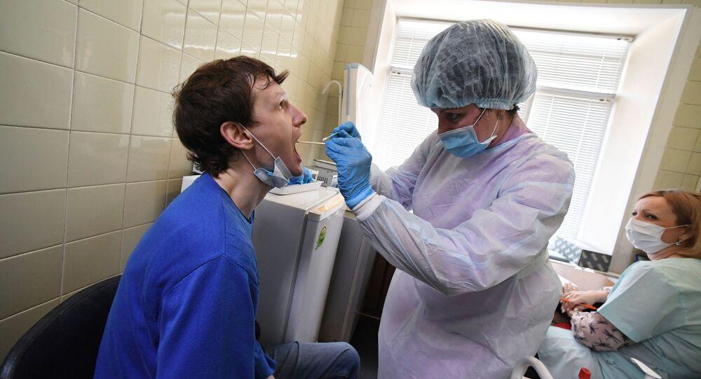 Epidemiolog pobiera wymaz z błony śluzowej jamy ustnej pacjenta w celu wykonania testu na koronawirusa we Władywostoku