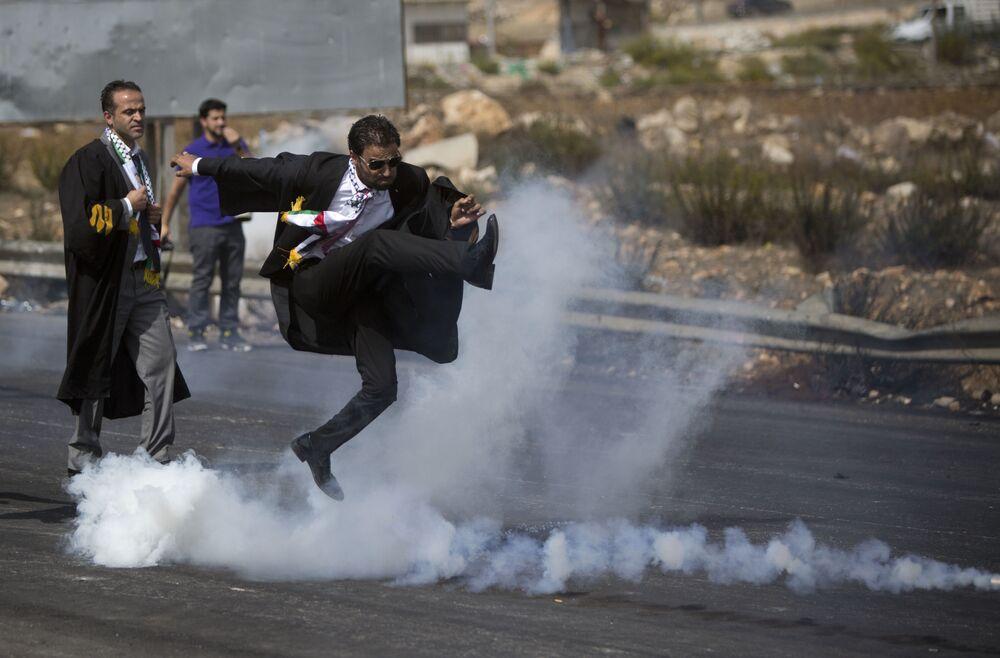Palestyński adwokat kopie balon z gazem łzawiącym podczas akcji protestacyjnej w mieście Ramallach