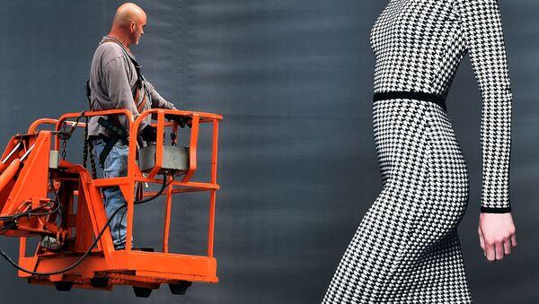 Разнорабочий рассматривает девушку на рекламном билборде Dressbarn в Нью-Йорке - Sputnik Polska