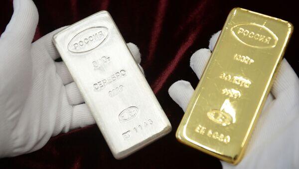 Pracownik trzyma sztabkę srebra i złota, które zostały wyprodukowane podczas otwarcia nowej linii produkcji sztabek w fabryce w Jekaterynburgu - Sputnik Polska