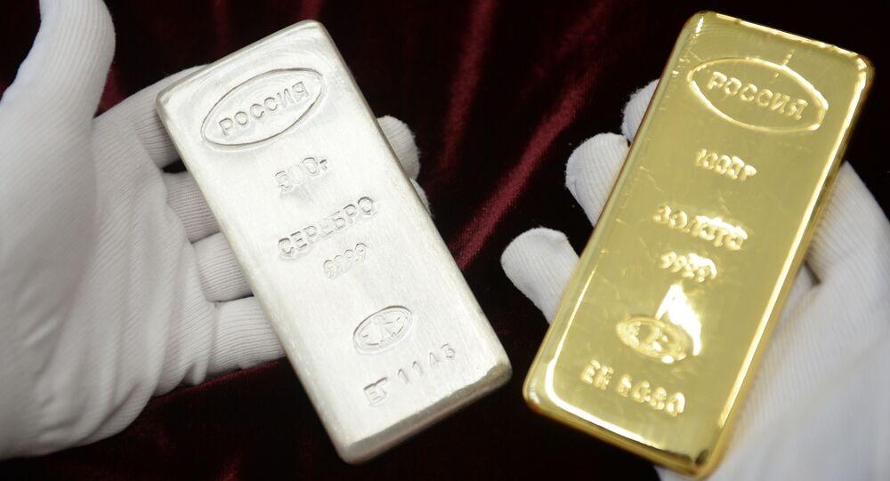 Pracownik trzyma sztabkę srebra i złota, które zostały wyprodukowane podczas otwarcia nowej linii produkcji sztabek w fabryce w Jekaterynburgu
