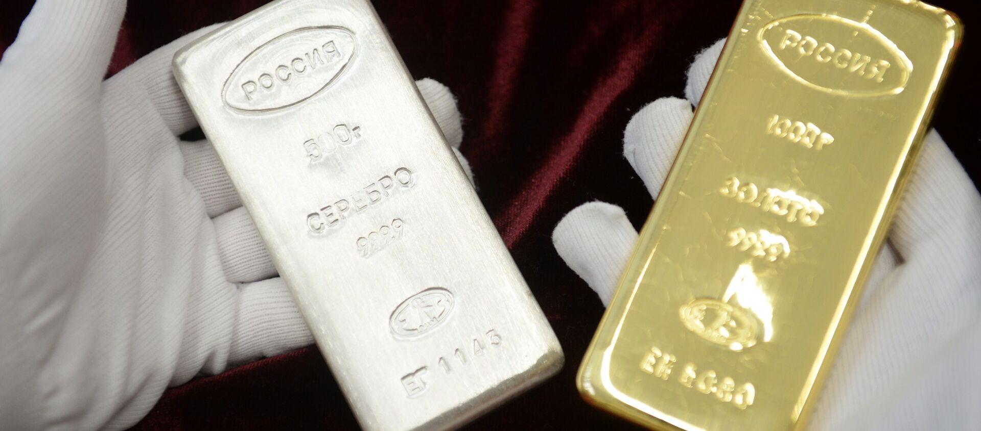 Pracownik trzyma sztabkę srebra i złota, które zostały wyprodukowane podczas otwarcia nowej linii produkcji sztabek w fabryce w Jekaterynburgu - Sputnik Polska, 1920, 04.11.2020