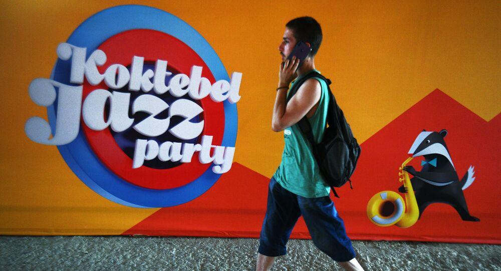 Młody człowiek na tle plakatu corocznego międzynarodowego festiwalu jazzowego Koktebel Jazz Party w Koktebelu