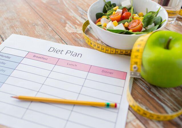 Sałatka, jabłko, ołówek i centymetr na tle planu żywieniowego
