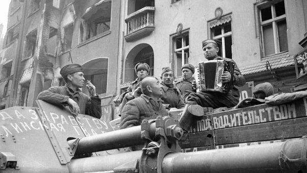 Żołnierze radzieccy słuchają akordeonu na ulicach Berlina, 1945 rok - Sputnik Polska