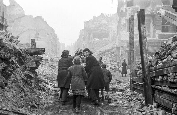 Mieszkańcy Berlina wracają do domu wzdłuż rozrzuconej gruzem ulicy, 1945 rok - Sputnik Polska