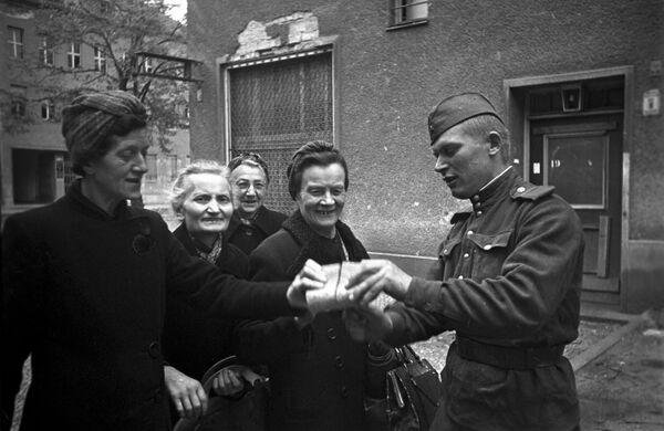 Radziecki żołnierz rozdaje chleb kobietom z Berlina, 7 maja 1945 rok - Sputnik Polska