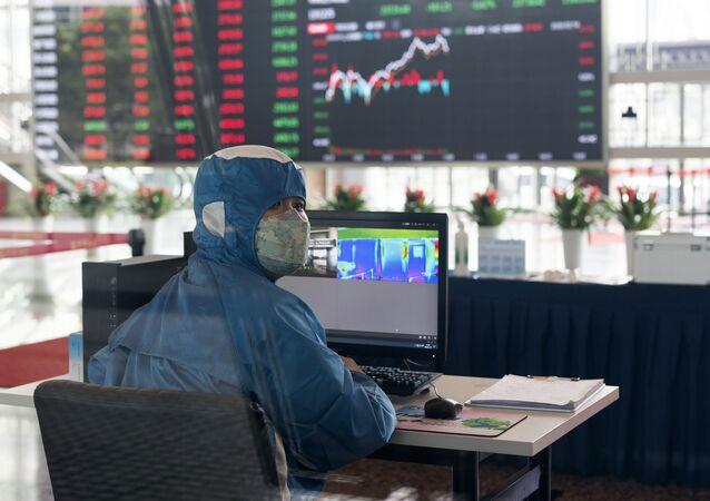 Pracownik w stroju ochronnym w holu giełdy w Szanghaju, Chiny