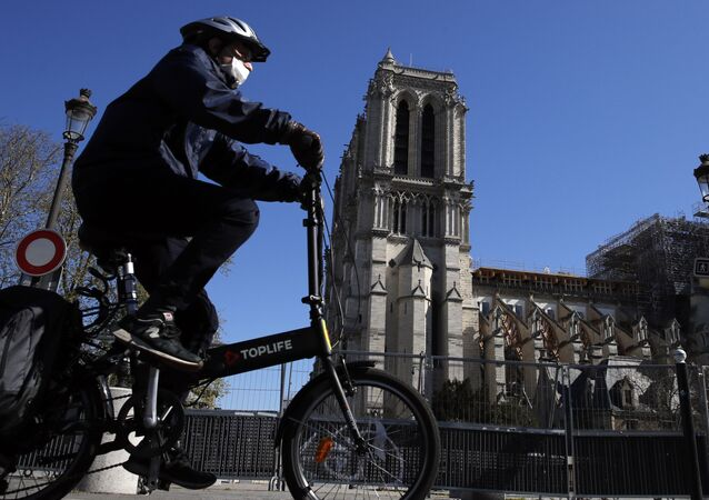 Rowerzysta przed katedrą Notre Dame w Paryżu