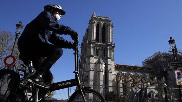 Rowerzysta przed katedrą Notre Dame w Paryżu  - Sputnik Polska