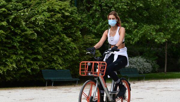 Dziewczyna w masce na rowerze - Sputnik Polska