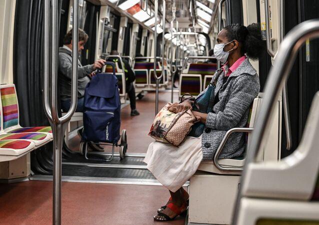 Pasażerowie w opustaszołym wagonie paryskiego metra w okresie pandemii
