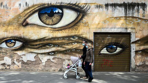 Para w maskach medycznych i z wózkiem obok graffiti w Rzymie, we Włoszech - Sputnik Polska
