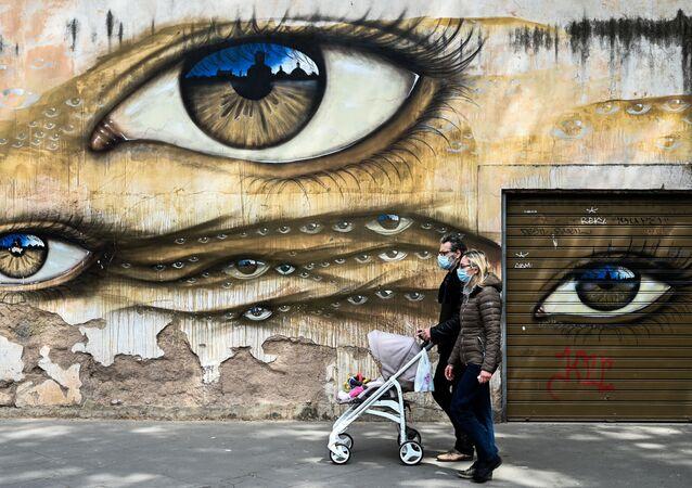 Para w maskach medycznych i z wózkiem obok graffiti w Rzymie, we Włoszech