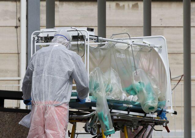 Włoscy lekarze przewożą chorego w specjalnym boksie