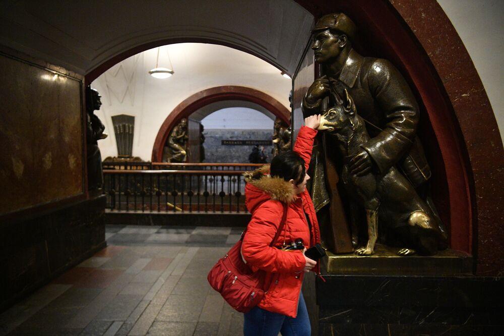 """Dziewczyna i rzeźba Zwiadowcy z psem na stacji """"Płoszczad Rewolucji"""""""