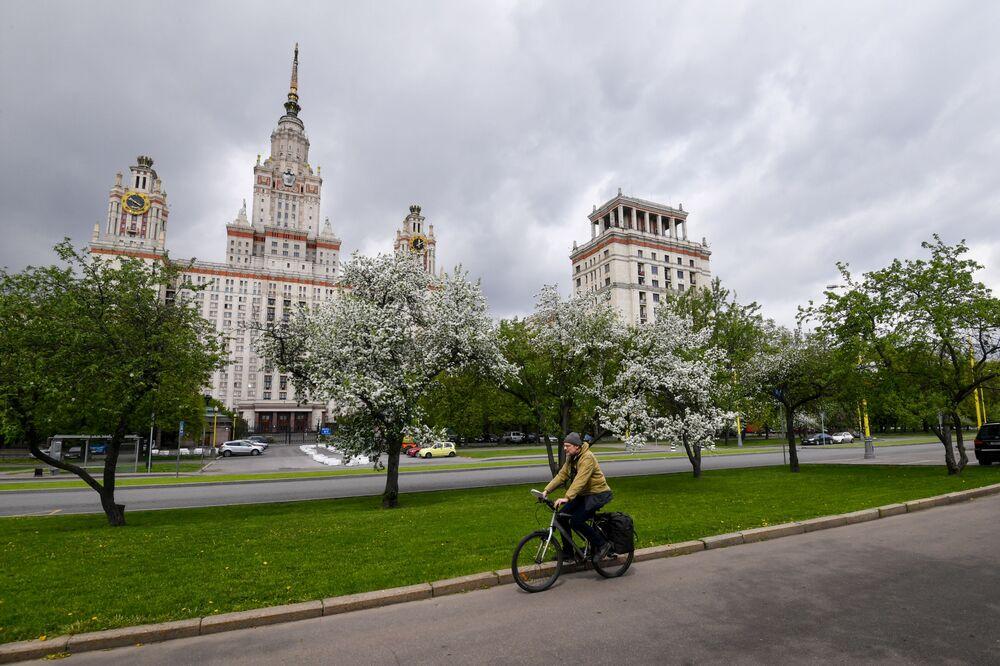 Rowerzysta na tle kwitnących drzew w pobliżu Moskiewskiego Uniwersytetu Państwowego w Moskwie.