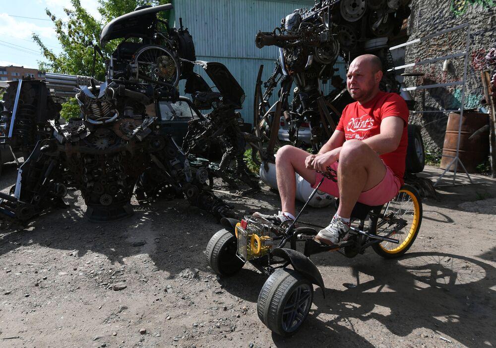 Mechanik samochodowy Siergiej Kulagin testuje dziecięcy trójkołowy rower własnego projektu