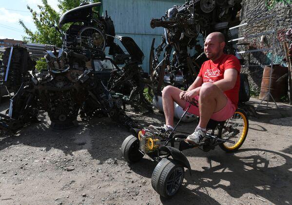 Mechanik samochodowy Siergiej Kulagin testuje dziecięcy trójkołowy rower własnego projektu - Sputnik Polska
