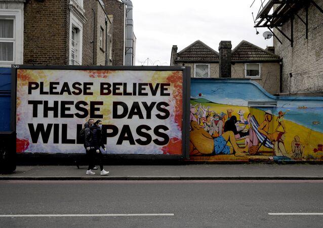 Przechodnie w maskach medycznych na tle graffiti w Londynie w Wielkiej Brytanii