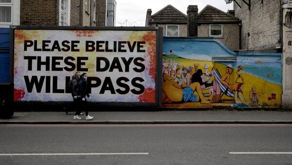 Przechodnie w maskach medycznych na tle graffiti w Londynie w Wielkiej Brytanii - Sputnik Polska