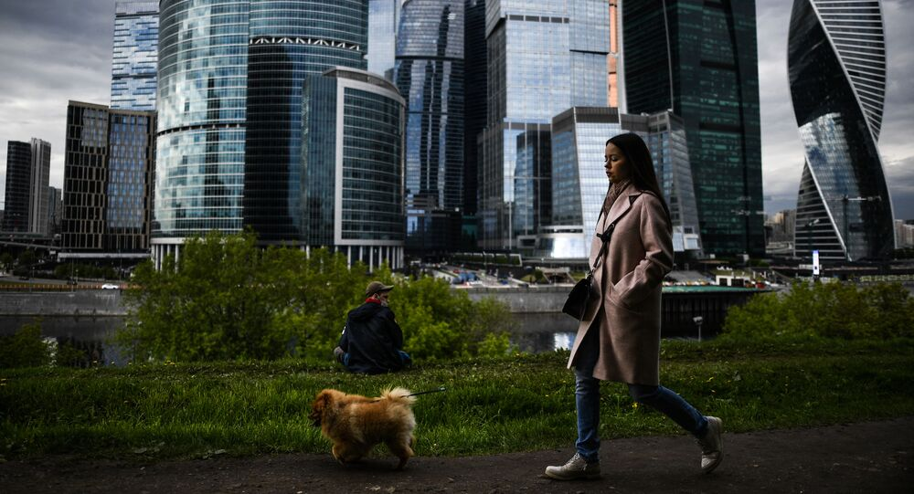 Dziewczyna spaceruje z psem po promenadzie Tarasa Szewczenki w Moskwie