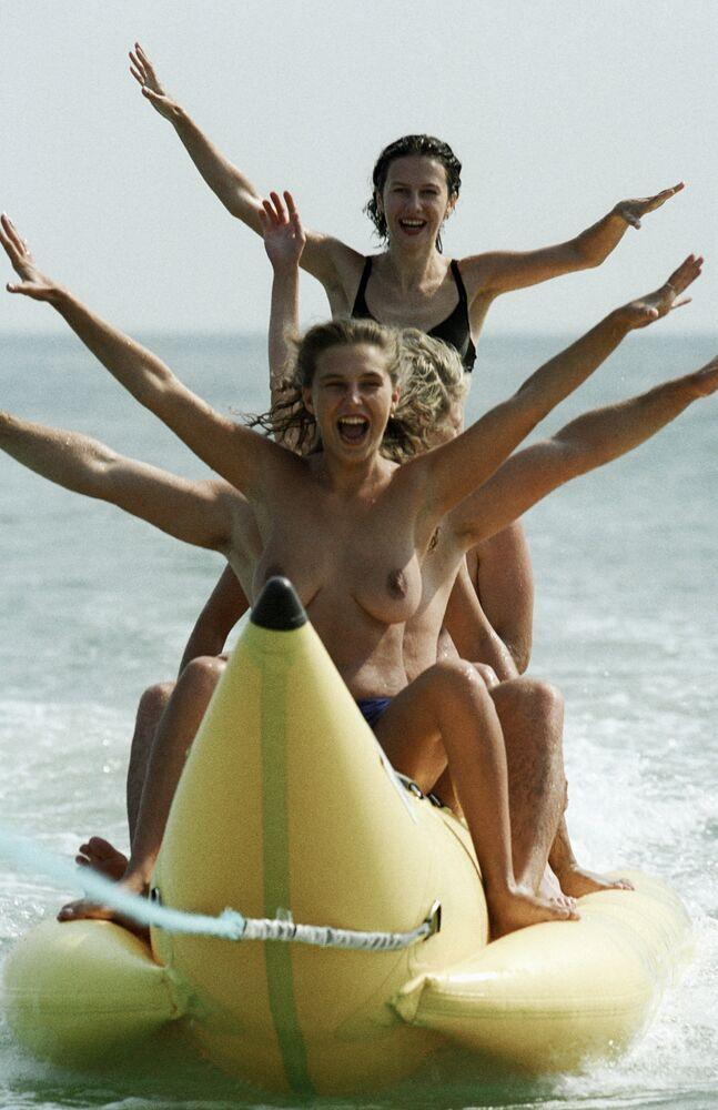 Dziewczyny jeżdżą na dmuchanym bananie podczas urlopu nad Morzem Czarnym