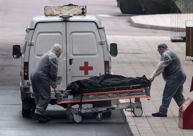 Pracownicy medyczni transportują ciało zmarłego do centrum kwarantanny w Kommunarce