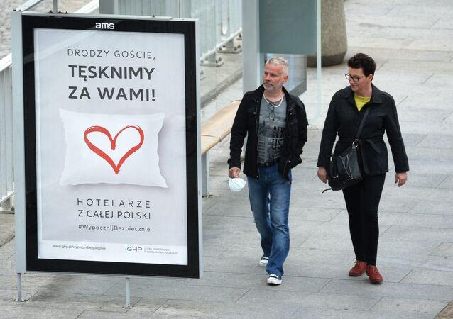 Mieszkańcy Warszawy podczas epidemii koronawirusa. Obok zabawny plakat o branży hotelowej