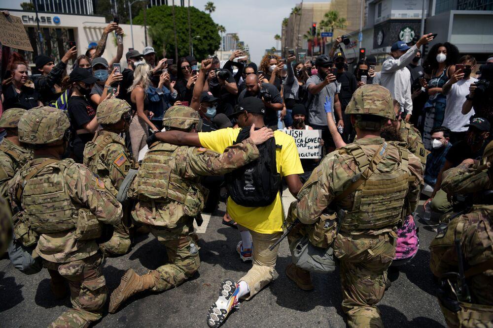 Protestujący i funkcjonariusze Gwardii Narodowej USA klęczący podczas demonstracji śmierci George'a Floyda w Los Angeles