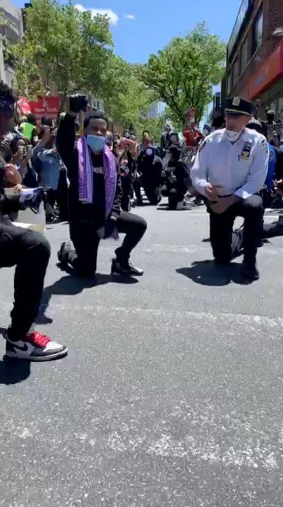 Policja klęczy razem z protestującymi w Queens, Nowy Jork, USA