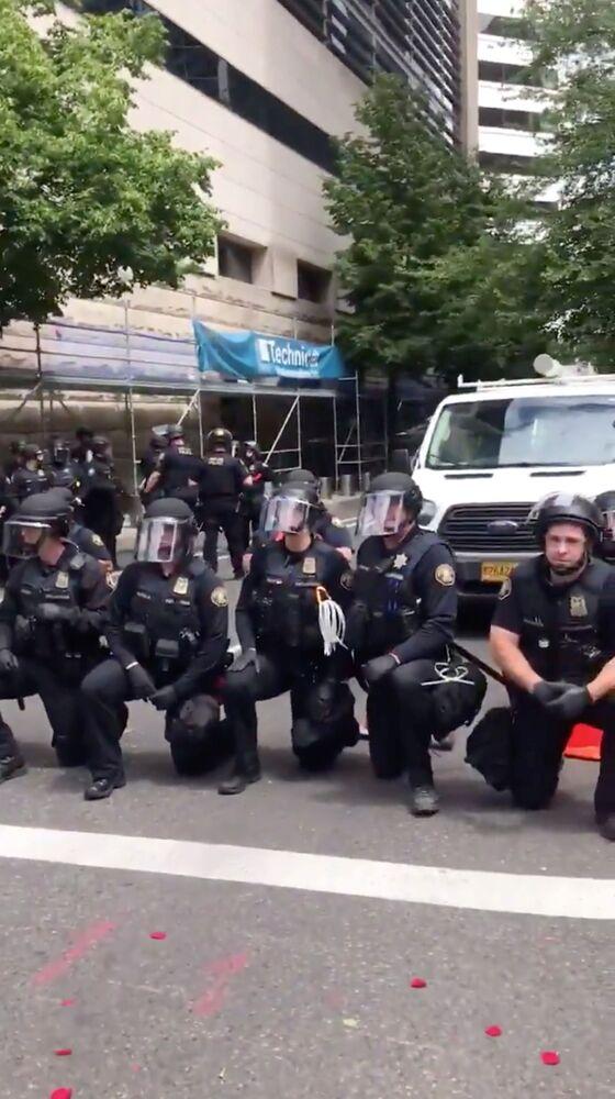 Funkcjonariusze policji klęczący w solidarności z protestującymi w Portland, USA