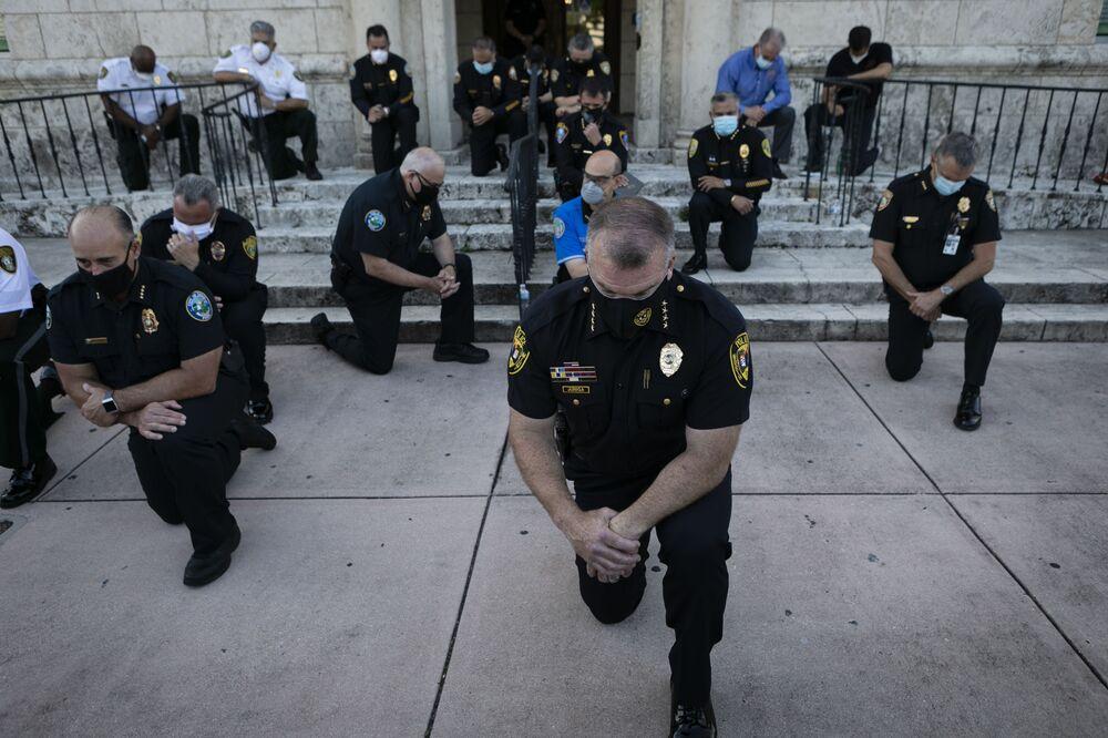 Policjanci klęczący podczas wiecu w Coral Gables na Florydzie