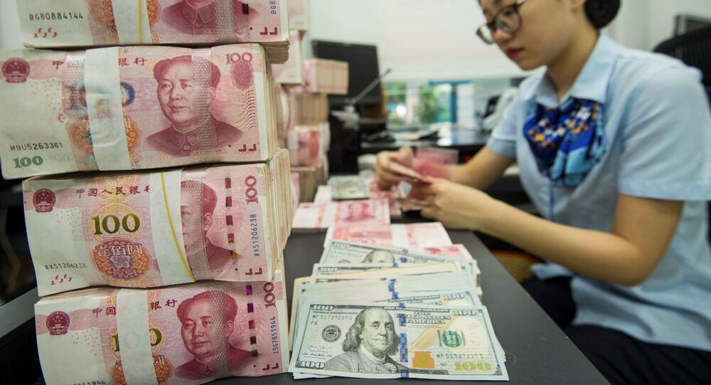 Pracownica banku liczy dolary i juany