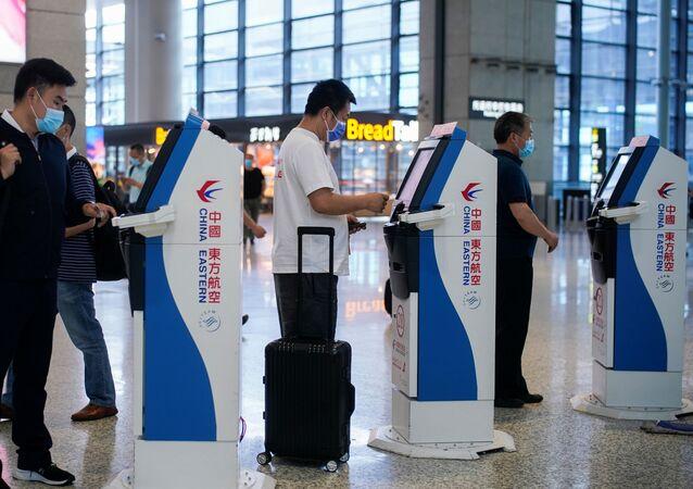 Ludzie w maskach ochronnych na lotnisku w Szanghaju