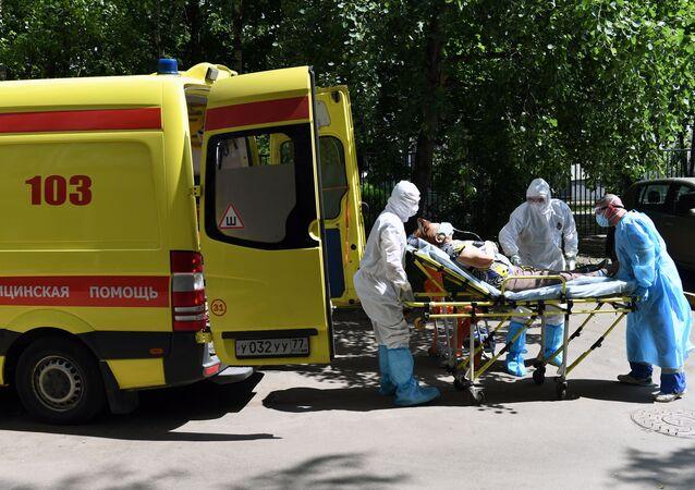 Sanitariusze i kierowca przenoszą pacjenta z podejrzeniem koronawirusa do karetki pogotowia