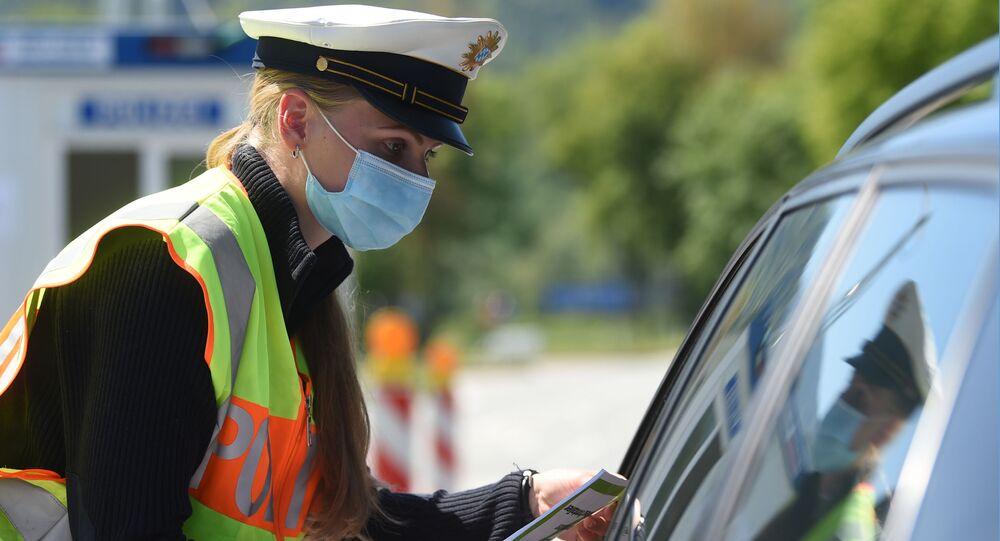 Niemiecki policjant w masce ochronnej podczas sprawdzania samochodu na przejściu granicznym między Austrią a Niemcami