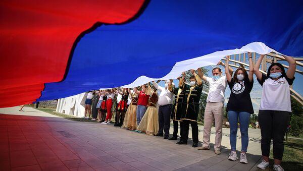 Uczestnicy obchodów Dnia Rosji trzymają rosyjską flagę w Parku Przyjaźni miasta Gieorgijewsk - Sputnik Polska