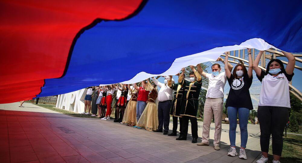 Uczestnicy obchodów Dnia Rosji trzymają rosyjską flagę w Parku Przyjaźni miasta Gieorgijewsk