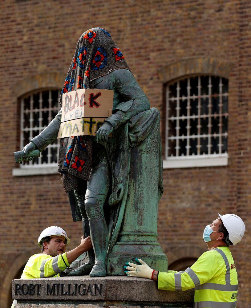 """Robotnicy usuwają statuę Roberta Milligana, nakrytą płachtą z napisem """"Black Lives Matter"""", Londyn, Wielka Brytania."""